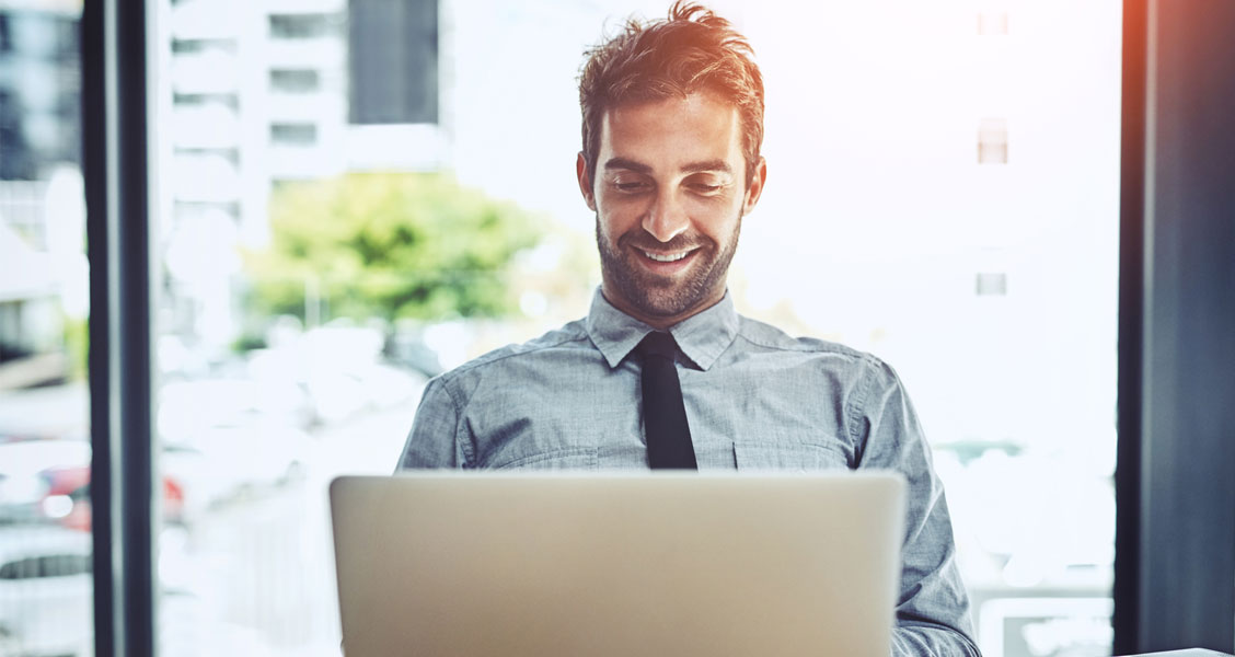 Man sitting at office desk and typing on laptop