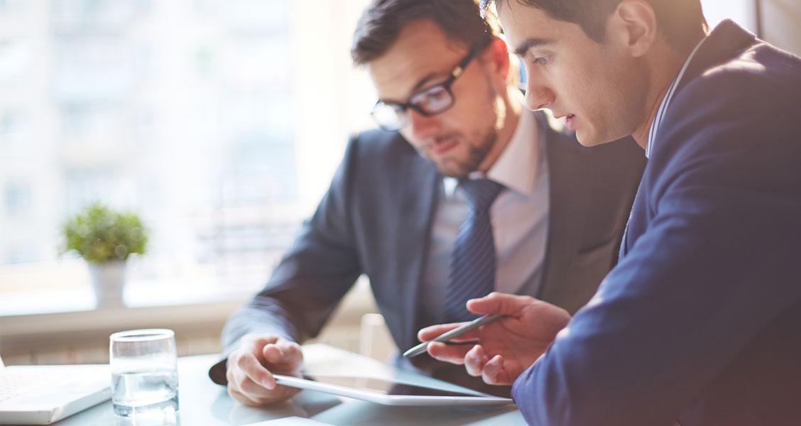 Two men talking at an office desk