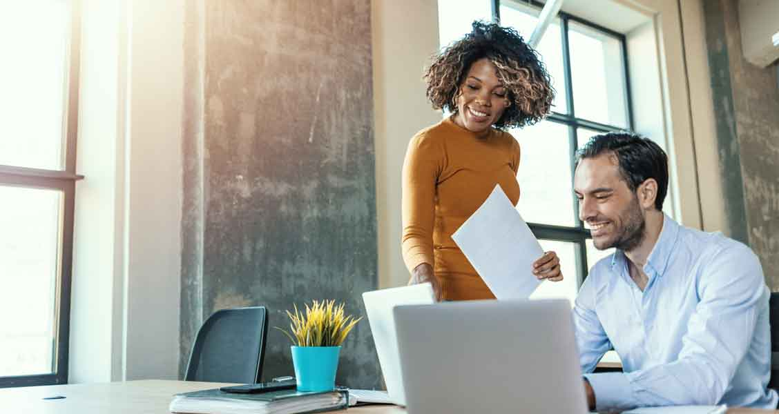woman and man working on something together in an office