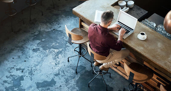 Man typing on laptop at desk