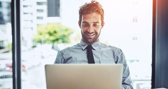 Man sitting at laptop and smiling